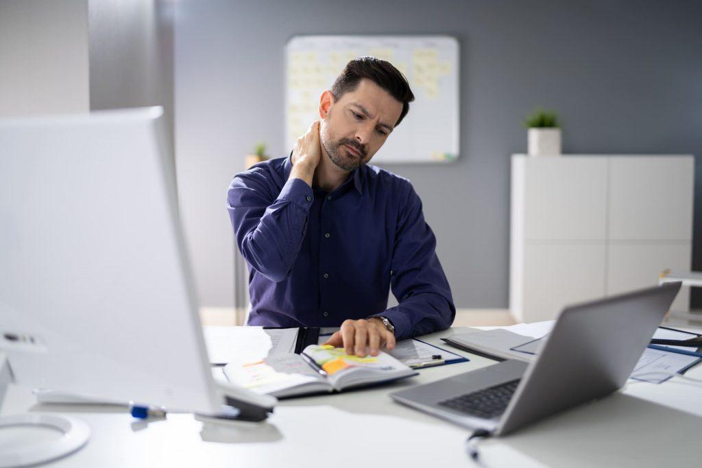 man holding neck sitting at desk