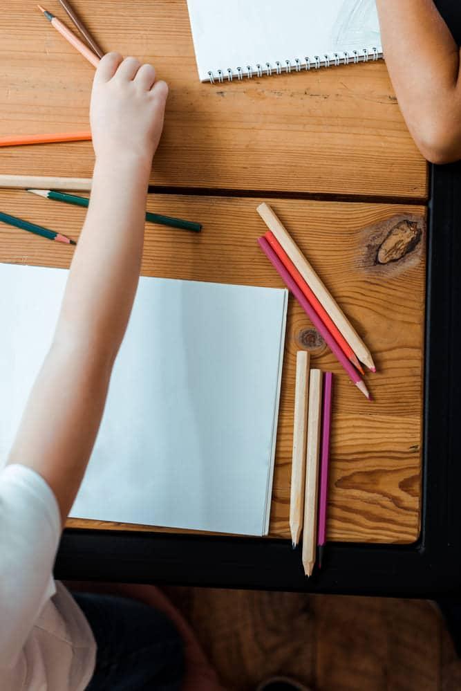 kid drawing at desk