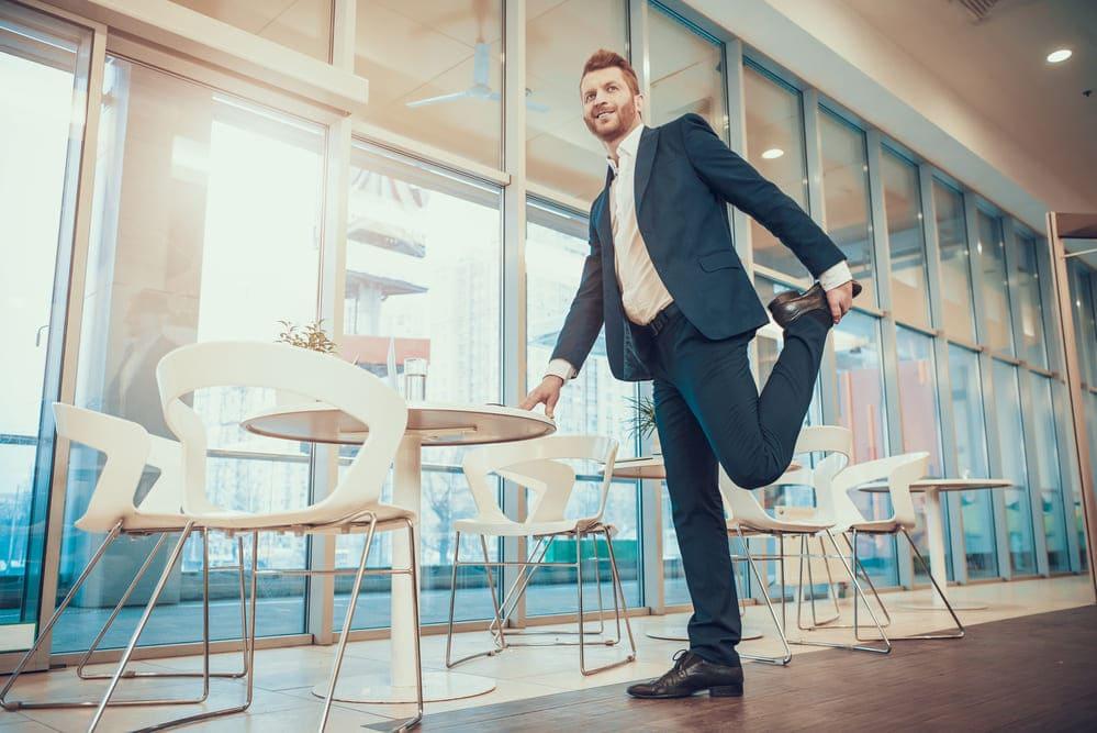 man stretching leg at office